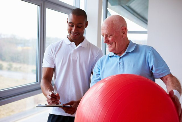 Physiotherapist going over gym ball exercise for the spine and joint.
